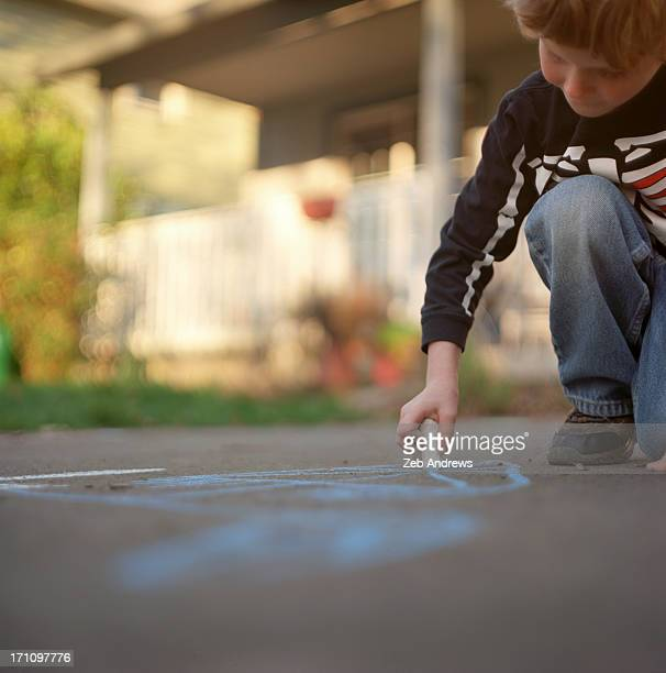 Young boy practices being a chalk artist