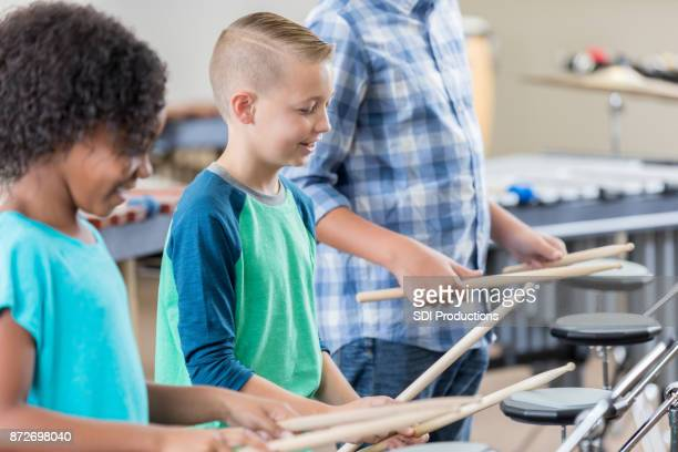 Young boy practices drums with teacher and schoolmate