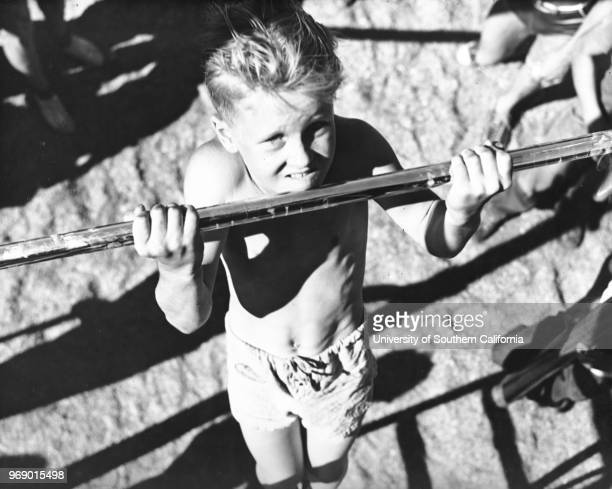 A young boy practices his chinups on one of many playground bars Los Angeles California early to mid twentieth century