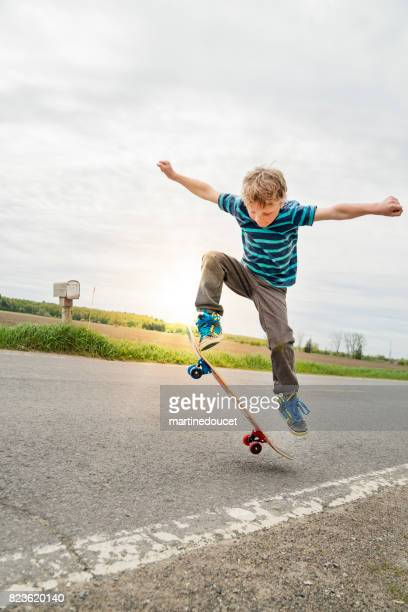 Young boy practicing skateboard in rural street.