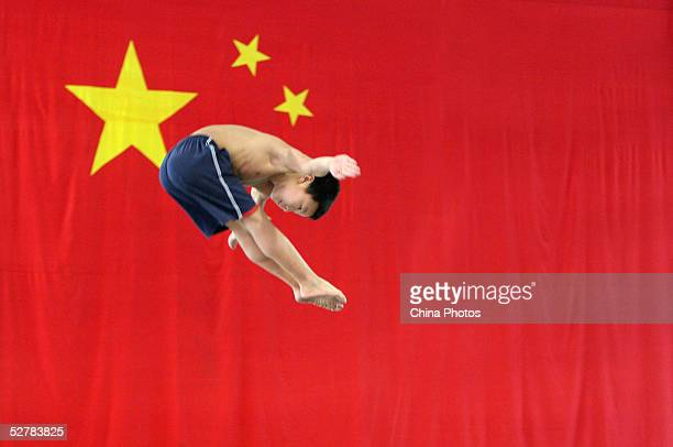A young boy practises diving movements as he jumps on a trampoline in front of a national flag at a diving school on May 10 2005 in Chengdu of...