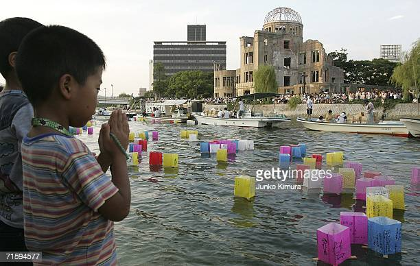 A young boy prays after releasing a floating lantern onto the Motoyasu river in front of the Atomic Bomb Dome for the victims of the bomb and for...