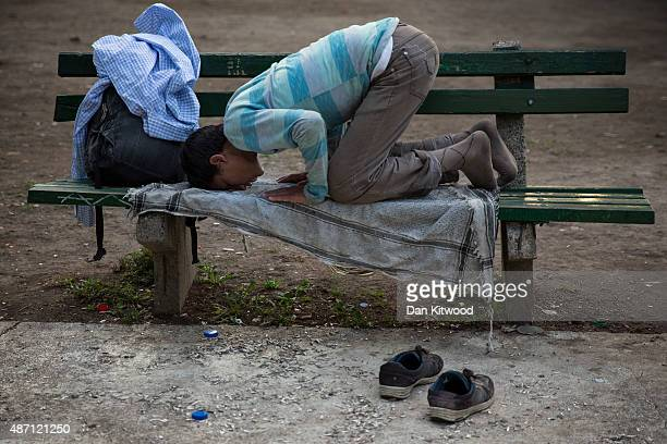 A young boy prays on a park bench in a public park near the train station September 6 2015 in Belgrade Serbia Many migrants short on financial...