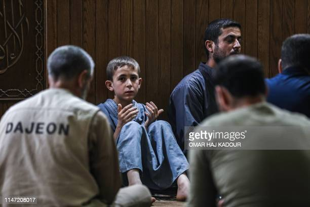 A young boy prays with other Muslim worshippers at a mosque in Maaret alNoman in Syria's northwestern Idlib province early on June 1 on the occasion...