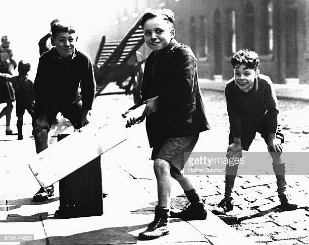 A young boy prepares to hit the ball during a match in a London street