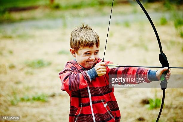 Young boy preparing to shoot bow and arrow