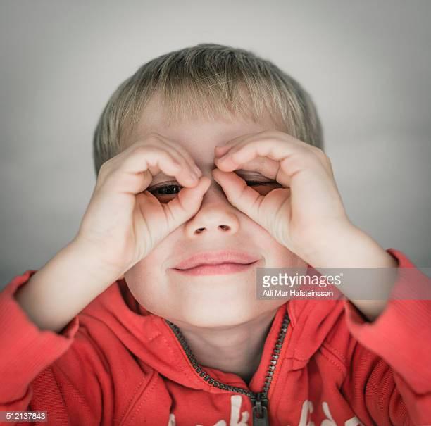 Young boy pretending to wear glasses, portrait