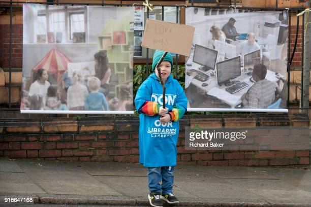 A young boy protests outside Carnegie Library on Herne Hill in south London which reopens for the first time in almost 2 years on 15th February 2018...