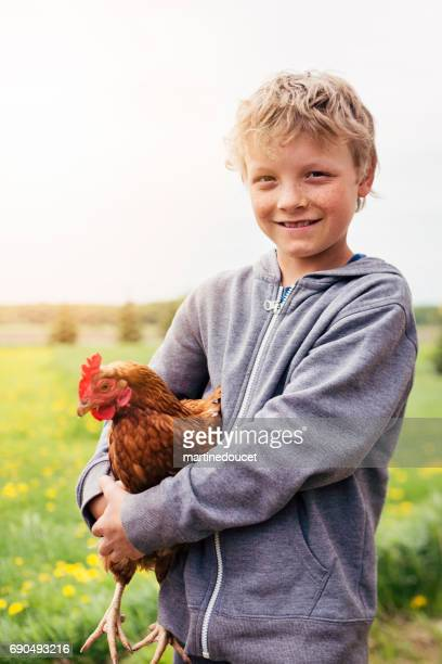 Young boy proudly holding a hen in a field.