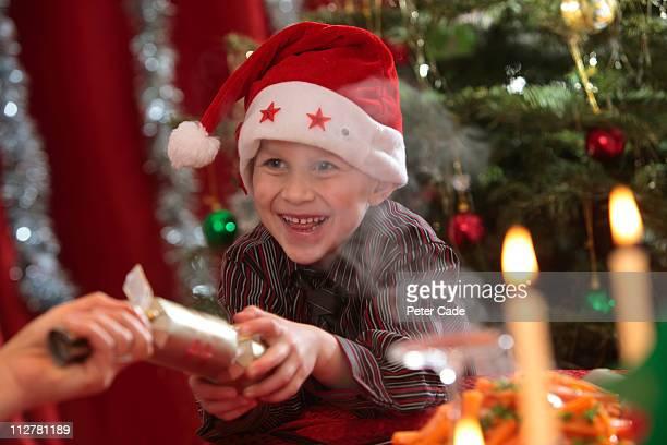 young boy pulling cracker at christmas table - クリスマスクラッカー ストックフォトと画像