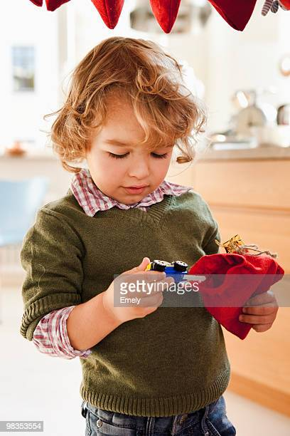 young boy pulling toy out of gift sack - advent calendar stock photos and pictures