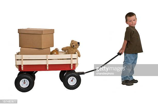 young boy pulling wagon with boxes and teddy bears - toy wagon stock photos and pictures