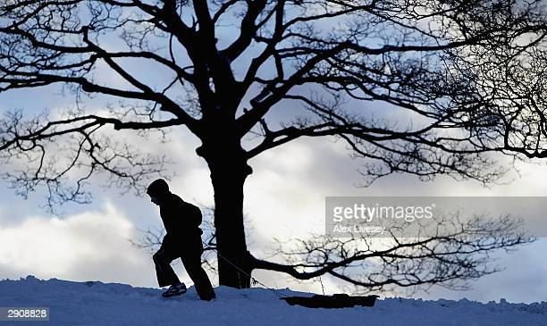 A young boy pulls his sled up the hill in Lyme Park Disley as enjoys the snow which hit the region January 28 2003 in Stockport England