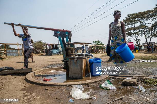A young boy pumps water from a borehole as a woman collects water into buckets in Glen View a suburb of Zimbabwe's capital Harare where the cholera...