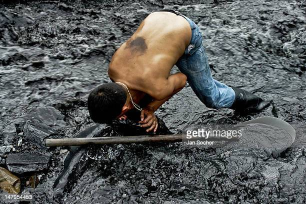 A young boy pushes a stone to find emeralds in the mine of Muzo on April 21 2006 in Muzo Colombia Despite of a persisting civil war conflict Colombia...