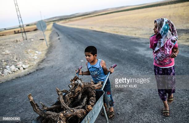 TOPSHOT A young boy pushes a wheelbarrow with wood next to a young girl on September 1 2016 the TurkishSyrian border town of Karkamis in the southern...