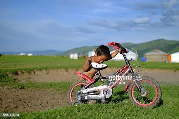 A young boy pushes his bicycle during the traditionnal Nadaam festival in a nomad camp in the Ovorkhangai province on July 18 2016 / AFP / JOEL SAGET