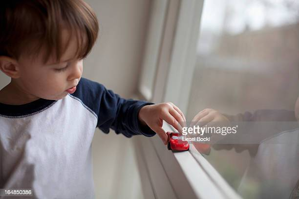 A young boy pushing a toy car along a window sill