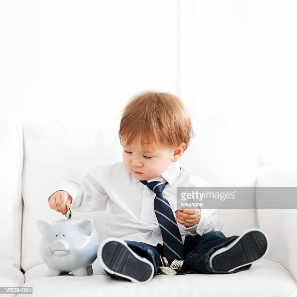 Young boy putting a coin into a white piggy bank