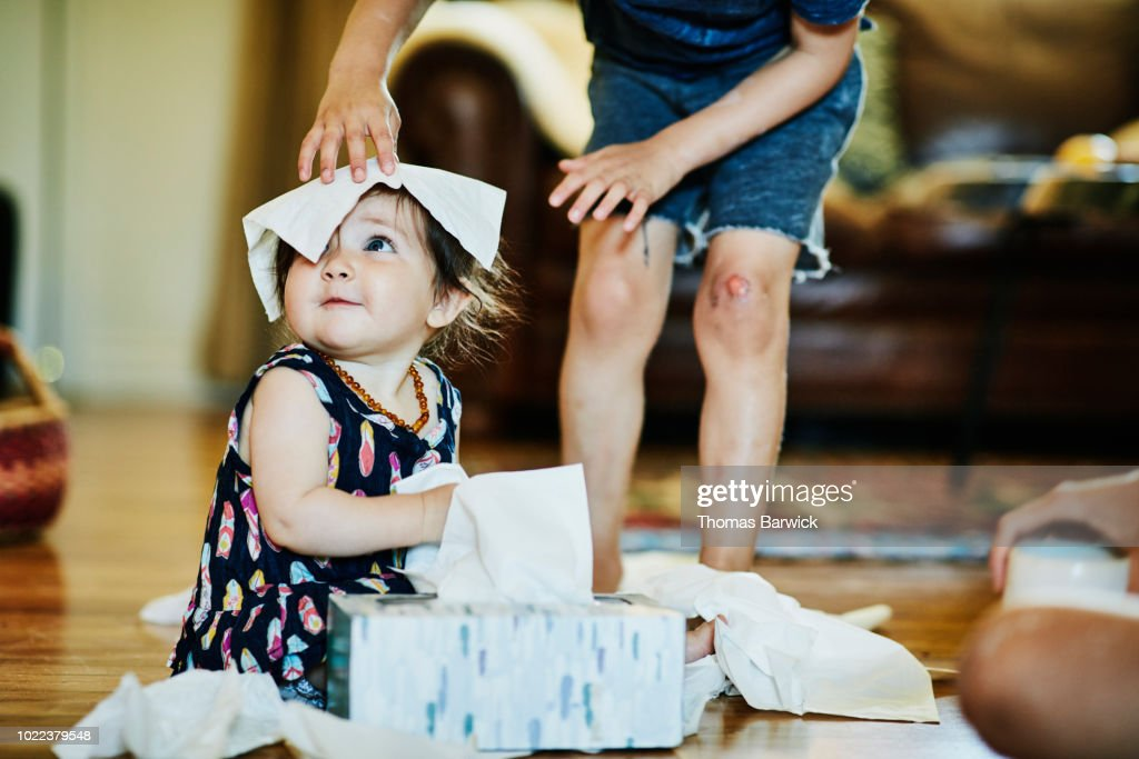 Young boy putting facial tissue on infant sisters head in living room : Stock Photo