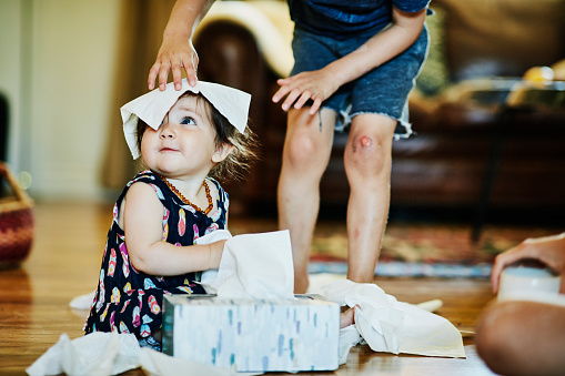 Young boy putting facial tissue on infant sisters head in living room - gettyimageskorea
