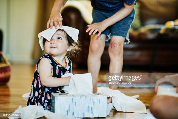 Young boy putting facial tissue on infant sisters head in living room