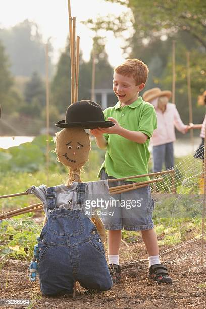 Young boy putting hat on scarecrow
