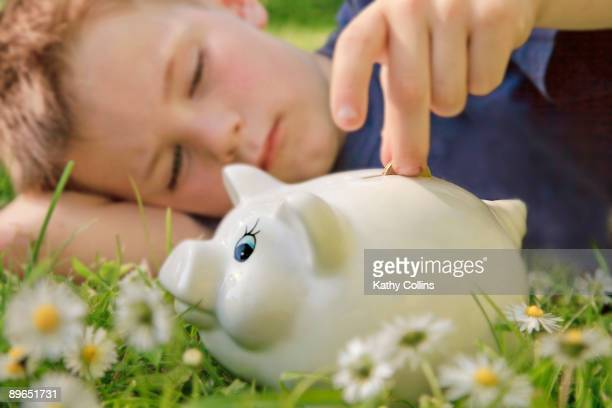 young boy putting money into piggy bank - kathy cash stock pictures, royalty-free photos & images