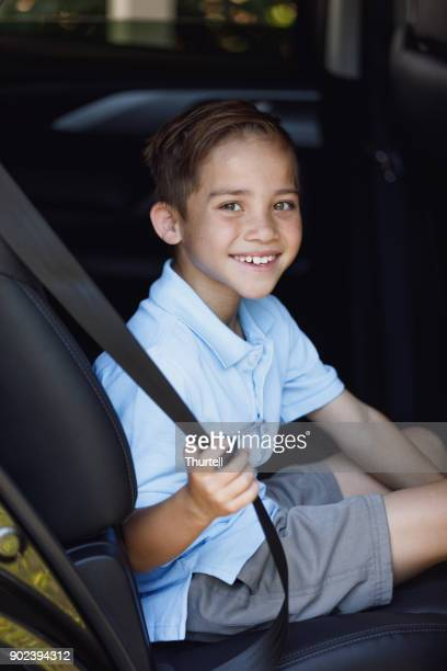 Young Boy Putting On Seat Belt