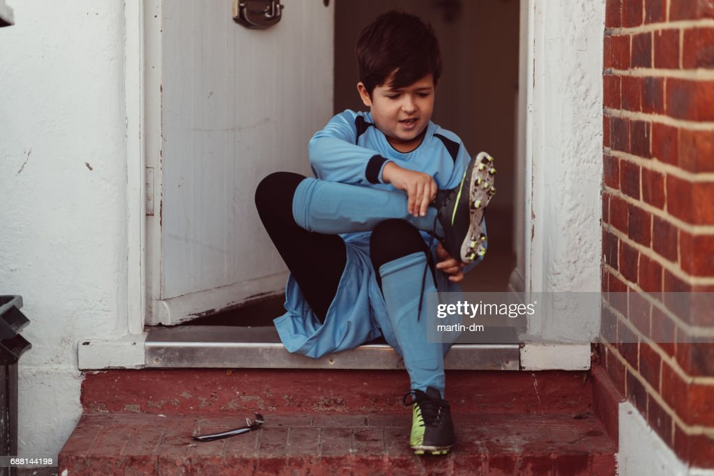 Young boy putting sports shoes at the doorstep : Stock Photo