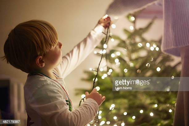 Young boy putting up christmas tree lights