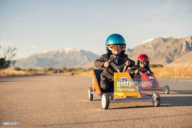 Jeune garçon courses petite voiture portant costume d'affaires