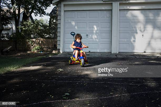 Young boy racing down driveway on tricycle.