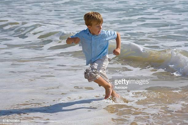 Young boy racing from an incoming wave. Mooloolaba, Sunshine Coast, Queensland, Australia.