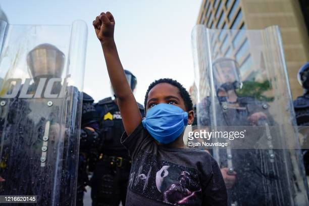 Young boy raises his fist for a photo by a family friend during a demonstration on May 31, 2020 in Atlanta, Georgia. Across the country, protests...