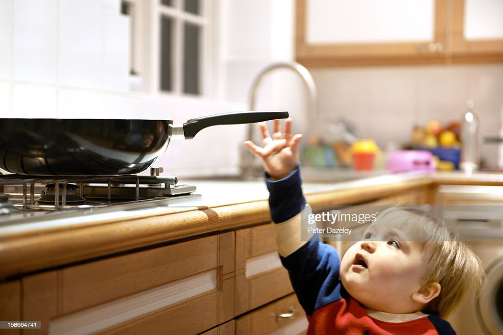 Young boy reaching for a hot pan on a hob : Stock Photo