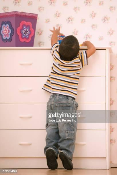 Young boy reaching on dresser