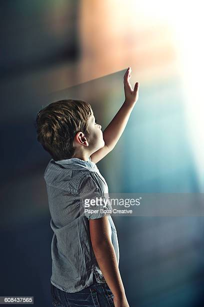 Young boy reaching up towards the light
