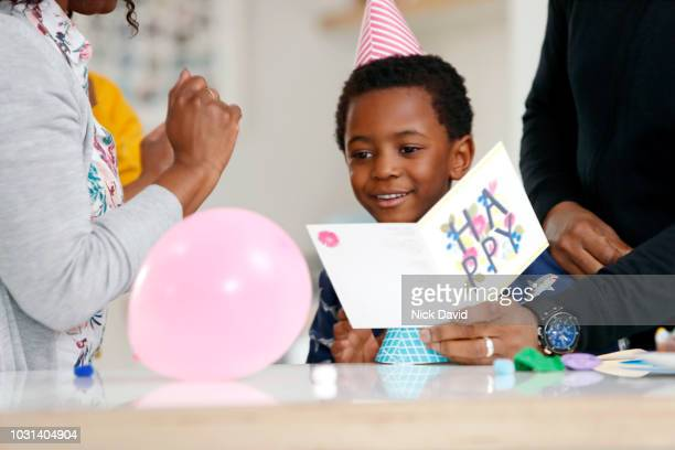 young boy reading birthday card - birthday card stock pictures, royalty-free photos & images