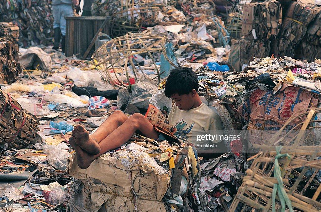 Young boy reading comic on Smokey Mountain,Manila,Philippines : Stock Photo
