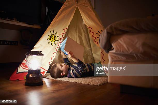 young boy reading inside tent set up indoors - teepee stock photos and pictures