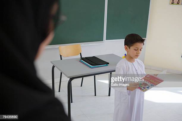 Young boy reading school book in front of teacher. Dubai, United Arab Emirates