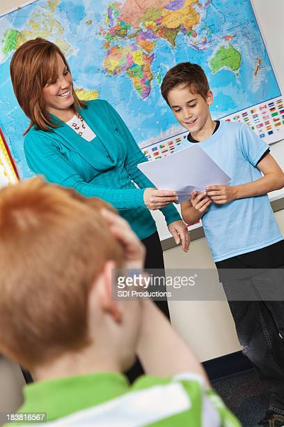 Young Boy Reading to Class With Teacher Helping Him