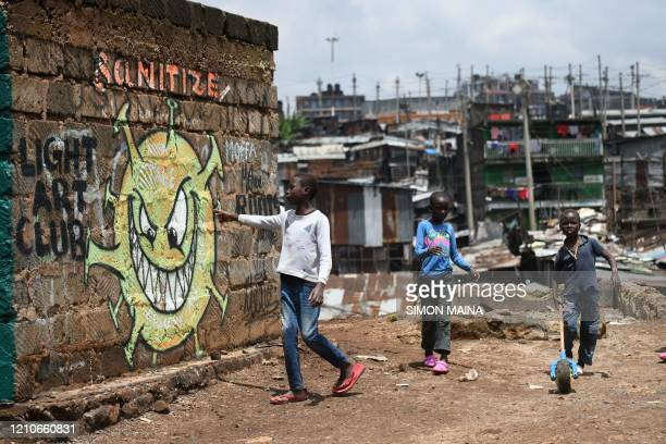 TOPSHOT A young boy reads out the message from an informational mural warning people about the risk of the COVID19 coronavirus in the Mathare valley...