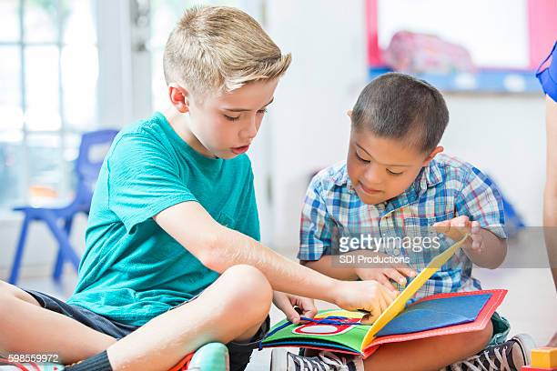 young boy reads to a preschooler with down syndrome - male friendship stock pictures, royalty-free photos & images