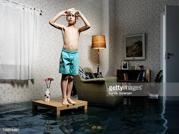 young boy ready to swim in flooded room