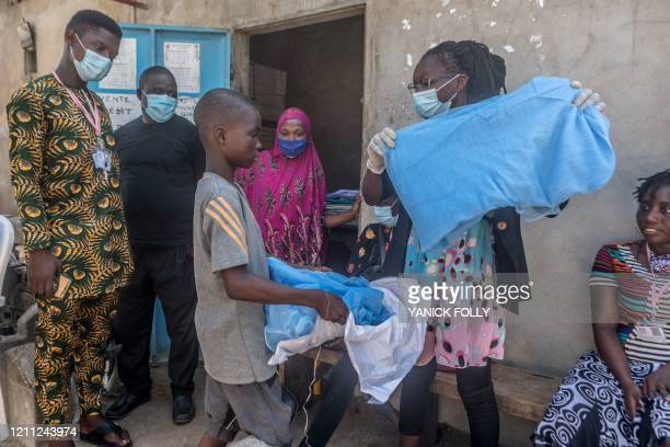 Young boy receives a mosquito net on April 28, 2020 in Cotonou during a distribution aiming at fighting malaria amid the pandemic of the novel...