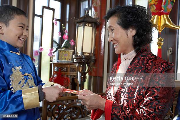 A young boy receives a red envelope with money inside from his grandmother during Chinese New Year.