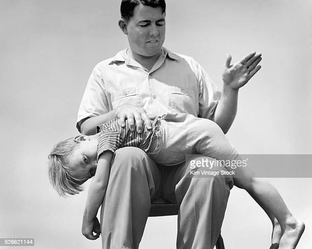 A young boy receives a spanking from his father in this staged photograph
