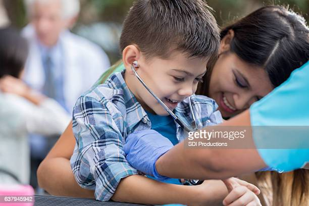 Young boy receives exam at free outdoor clinic